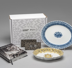 "<p>Includes the publication ""A Baixela de Sua Majestade Fidelíssima"", serving dish of Carlota Joaquina dinner set (replica of the collection of the Palácio Nacional da Ajuda), serving dish Albarrada (inspired by the azulejo panel ""Albarrada"" of Museu Nacional do Azulejo and two vouchers with free entry (one voucher / one person), in one of the 25 cultural facilities of the Direção-Geral do Património Cultural, valid for one year.</p>